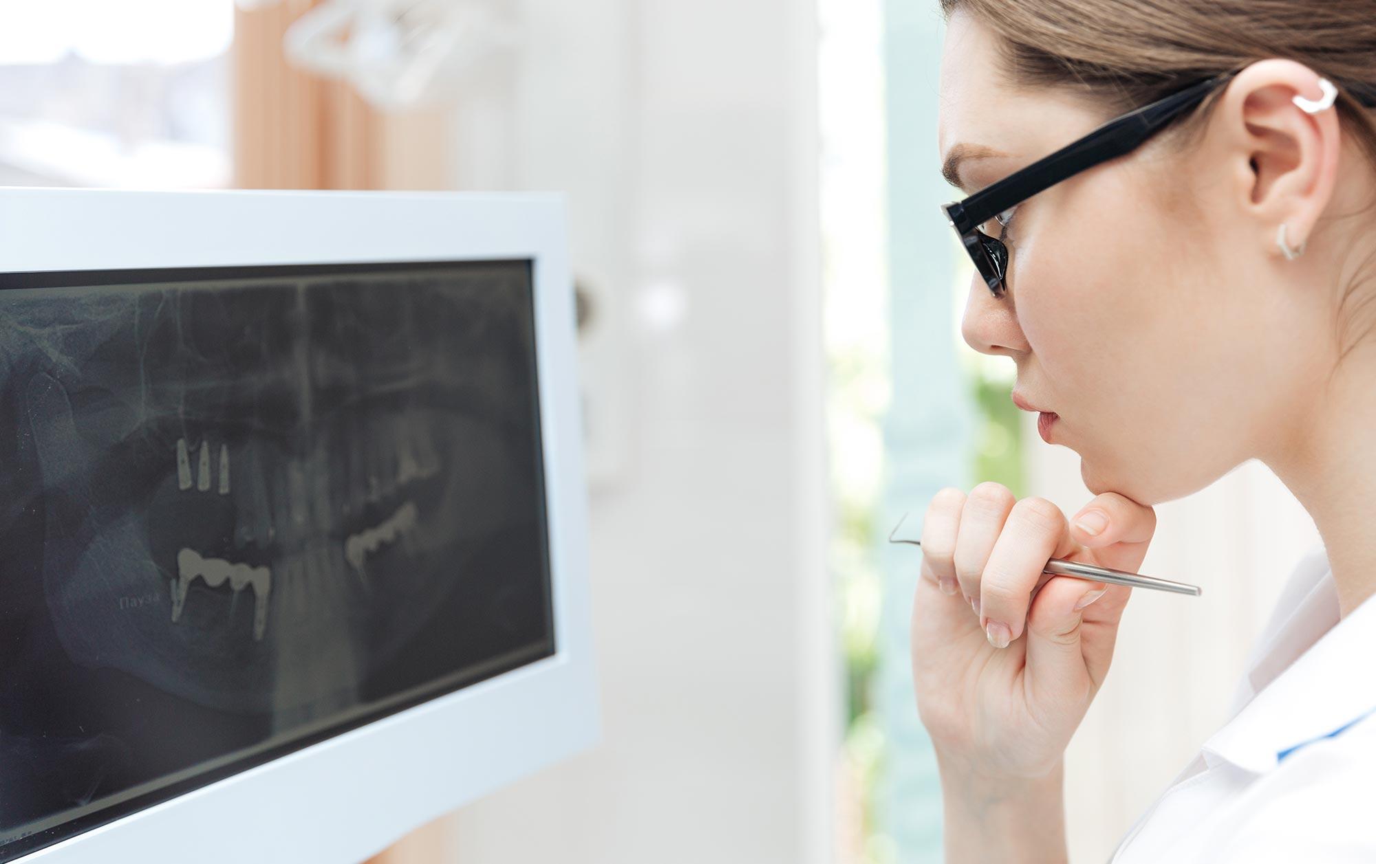 female dentist looking teeth on digital x-ray